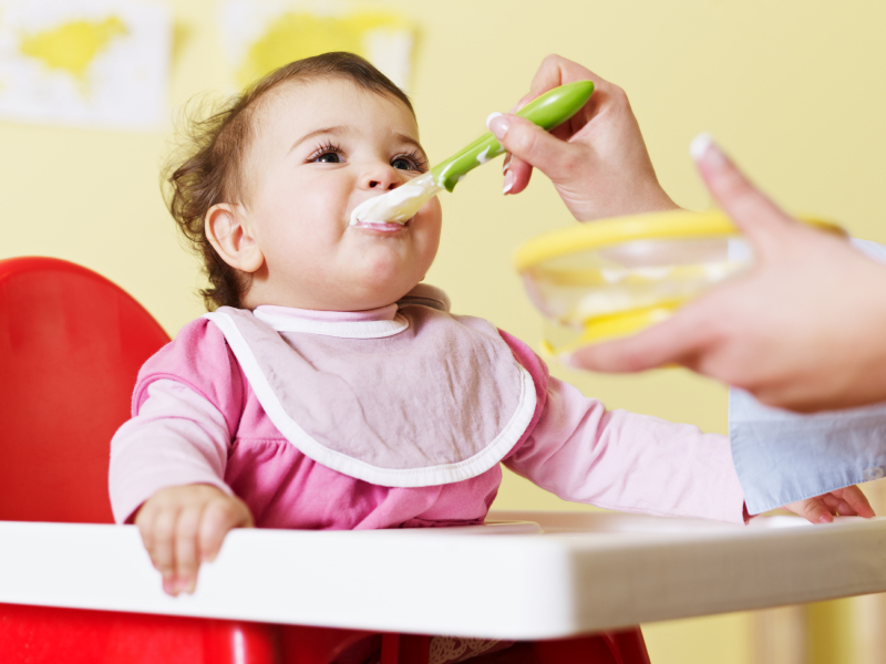 mom giving homogenized food to her daughter on high chair. Horizontal shape